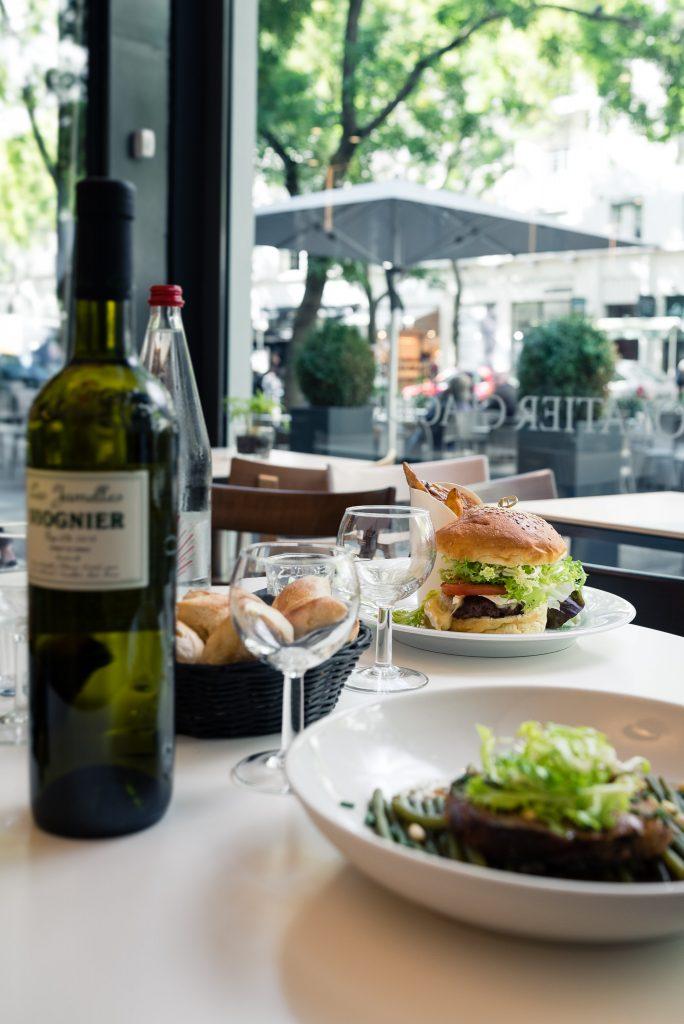 Assiette de salade et burger avec une bouteille de Viognier à La Table du Passage de la Maison Bettant à Villeurbanne